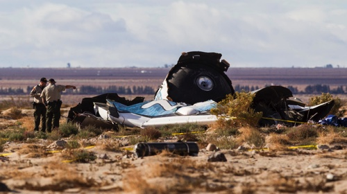 Law enforcement officers take a closer look at the wreckage near the site where a Virgin Galactic space tourism rocket exploded and crashed in Mojave, Calif.