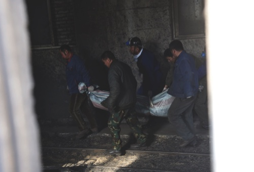 Rescuers carry the body of a victim from Hengda coal mine run by the state-owned Fuxin Coal Corp. in Fuxin, Liaoning province