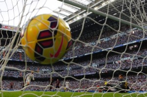 Real Madrid's Cristiano Ronaldo, left, scores his goal during a Spanish La Liga soccer match between Real Madrid and FC Barcelona at the Santiago Bernabeu stadium in Madrid