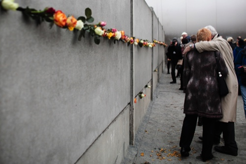 People hug each other after they put flowers in a crack of the former Berlin Wall to commemorate the victims of the wall at the Berlin Wall memorial site at Bernauer Strasse