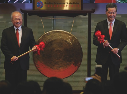 Hong Kong Exchanges and Clearing Ltd. Chairman Chow Chung-kong, left, and Hong Kong Chief Executive Leung Chun-ying pose before beating a gong during the launch ceremony of the Shanghai-Hong Kong Stock Connect in Hong Kong