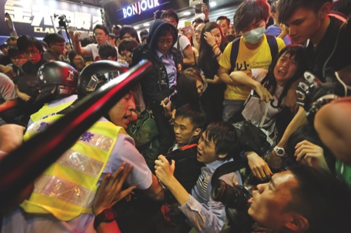 Police officers stop protesters blocking the road after police cleared barricades and tents in Mong Kok on Wednesday