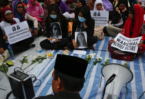 Jumiati, center left, cousin of Sumarti Ningsih and Susiati, center right, friend of Seneng Mujiasih, attend a vigil to demand justice for Ningsih and Mujiasih at a park in Hong Kong