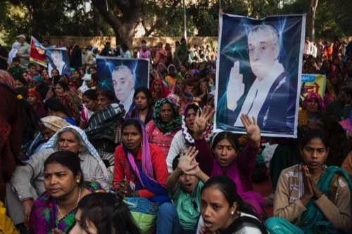 Supporters of controversial Indian guru Sant Rampal displaying his photographs, chant slogans praising him as they gather to show support at a protest venue near the Indian Parliament in New Delhi