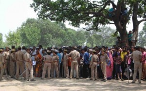 In this May 31, 2014, file photo, Indian policemen cordon off the area as villagers and others look toward the tree where two teenage girls were found hanging in Katra village in the northern state of Uttar Pradesh