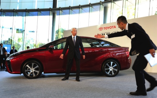 "Toyota Motor Corp. Executive Vice President Mitsuhisa Kato, left, is escorted after a photo session as Toyota unveils its all-new fuel cell vehicle, the ""Mirai"", in Tokyo"