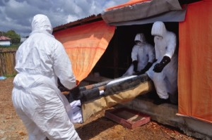 Ebola health care workers carry the body of a woman suspected of dying from Ebola
