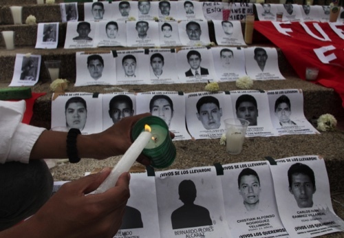 A woman lights a candle during a demonstration at the Angel of Independence, where the steps of the monument were lined with images of the 43 disappeared rural college students, in Mexico City