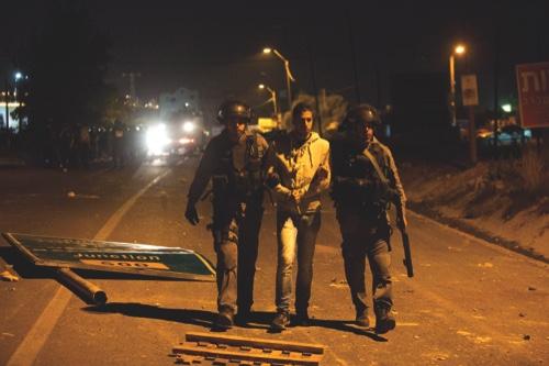 Israeli riot police officers arrest an Israeli Arab protester during a protest in the Arab village of Kfar Kana, northern Israel