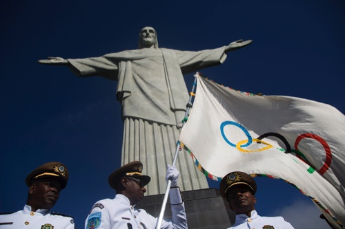 This Aug. 19, 2012, file photo shows the newly arrived Olympic flag in front of the Christ the Redeemer statue in Rio de Janeiro