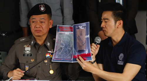 Thai police officers show pictures of a tattooed human skin during a press conference at Bangpongpang police station in Bangkok