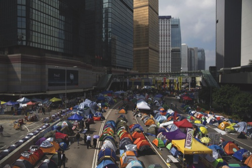 Pedestrians and demonstrators walk past tents outside the Central Government Offices in the Admiralty district