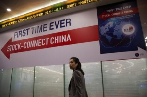 "A woman walks past a banner reading ""First Time Ever, Stock-Connect China"" during the launch ceremony of the Shanghai-Hong Kong Stock Connect"