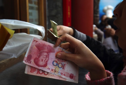 Customers hold Chinese yuan banknotes as they purchase Beijing ducks at a store in Beijing, China