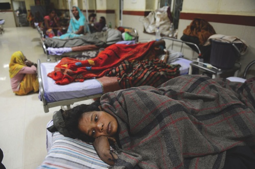 A woman who recently delivered a baby lies on a bed at a hospital in Shivpuri, in central Madhya Pradesh