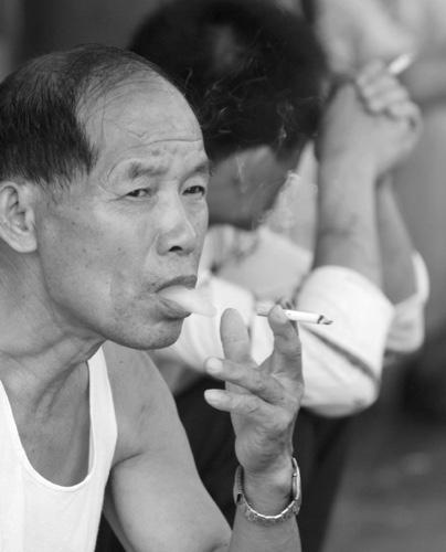2 Chinese men smoke on a street in Shanghai