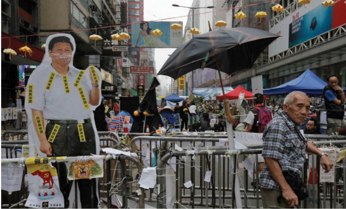 In this Nov. 4, 2014 file photo, a local resident stands next to a cut-out life-size photo of Chinese President Xi Jinping at a main road in the occupied area of the Mong Kok district in Hong Kong