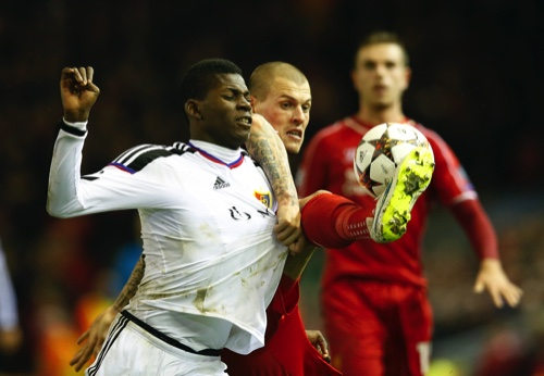 Basel's Breel Embolo, left, is challenged by Liverpool's Martin Skrtel during the Champions League Group B soccer match between Liverpool and FC Basel at Anfield Stadium in Liverpool