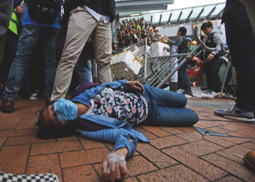 An injured protester lies on the ground during a police operation to remove protesters near government headquarters in Hong Kong yesterday