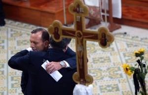 Ukraine's President Petro Poroshenko, right, and Australian Prime Minister Tony Abbott embrace during an ecumenical church service held at Ukrainian Greek Eparchy of Saints Peter and Paul in Melbourne