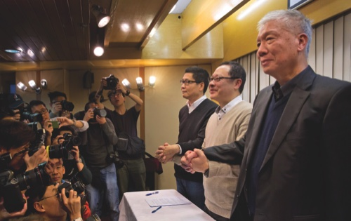Three protest leaders, from left, Chan Kin-man, Benny Tai Yiu-ting and Chu Yiu-ming, pose for photographers during a news conference in Hong Kong yesterday