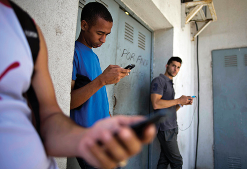 Students stand outside a building to find an Internet signal for their phones in Havana
