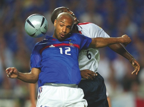 In this Sunday, June 13, 2004 file photo Thierry Henry, front, of France, is challenged by England's Sol Campbell during their the Euro 2004 Group B soccer match between England and France at Luz Stadium, in Lisbon, Portugal