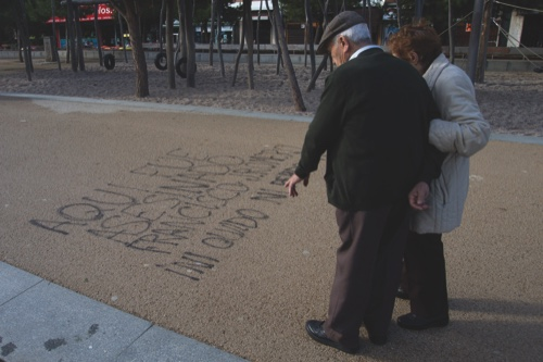 A couple stop to look at words painted on the ground by the Manzanarez river near where a 43-year-old Deportivo fan was killed