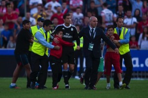 Real Madrid's Cristiano Ronaldo, center, is hugged by a young fan