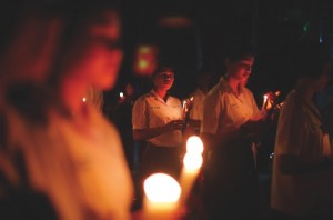 Thai schoolgirls hold candles as they observe a moment of silence for victims of the Asian tsunami during a commemoration service to mark the 10th anniversary in Ban Nam Khem