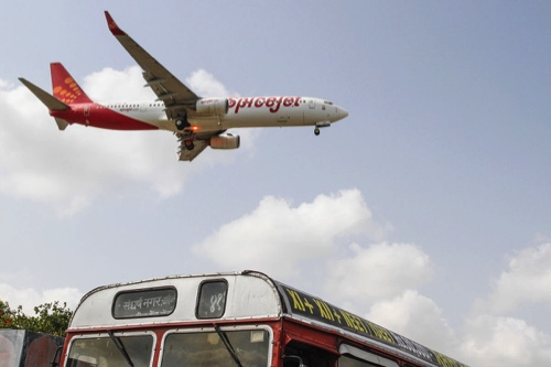 A SpiceJet Ltd. aircraft flies over a bus as it prepares to land at Chhatrapati Shivaji International Airport in Mumbai