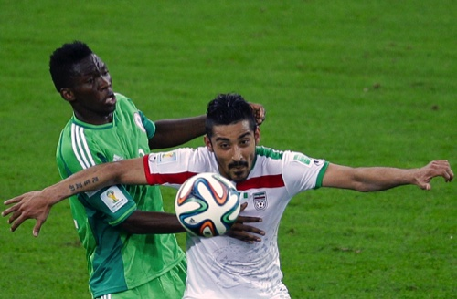 Iran's Reza Ghoochannejhad, right, challenges for the ball with Nigeria's Kunle Odunlami l during the group F World Cup soccer match between Iran and Nigeria at the Arena da Baixada in Curitiba, Brazil