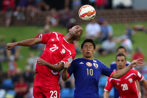 Palestine's Mural Said, left, and Japan's Shinji Kagawa attempt to head the ball during the AFC Asia Cup soccer match between Japan and Palestine in Newcastle, Australia