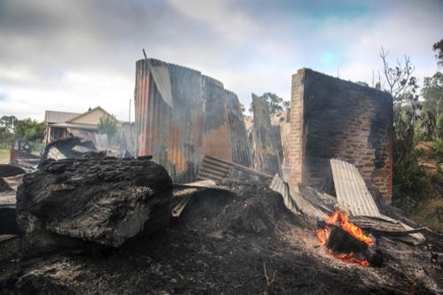 A few flames remain after a wildfire destroyed a building in the Adelaide Hills