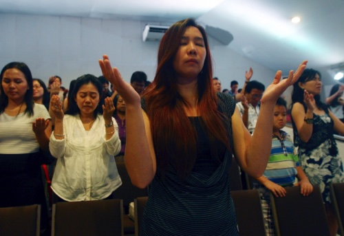 Members of Mawar Sharon church attend a prayer service for the relatives of lost loved ones aboard the AirAsia Flight 8501