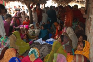 Indian women mourn around the bodies of two men, who died after consuming a bad batch of bootleg liquor in Datli village, about 30 km southwest of Lucknow