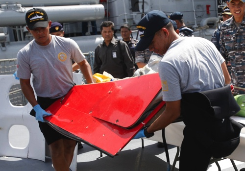 Crew members of Indonesian Navy ship KRI Bung Tomo carry a piece of the airplane part from AirAsia Flight 8501