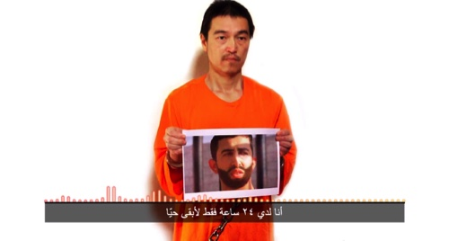 This still image taken from a video posted on YouTube by jihadists on Tuesday purports to show a still photo of Japanese journalist Kenji Goto holding what appears to be a photo of Jordanian pilot 1st Lt. Mu'ath al-Kaseasbeh