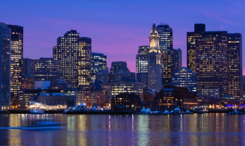 The Boston city skyline is illuminated at dusk as it reflects off the waters of Boston Harbor