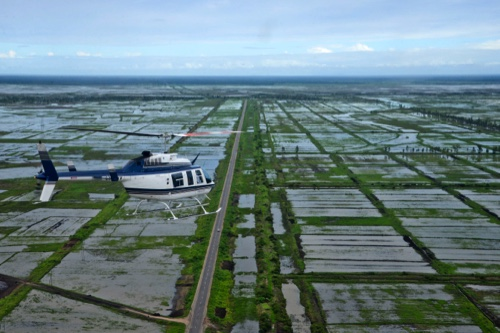 An helicopter flies over inundated fields in Mozambique