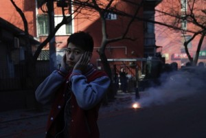 A man covers his ears as he walks past firecrackers set off by people on a street in Beijing