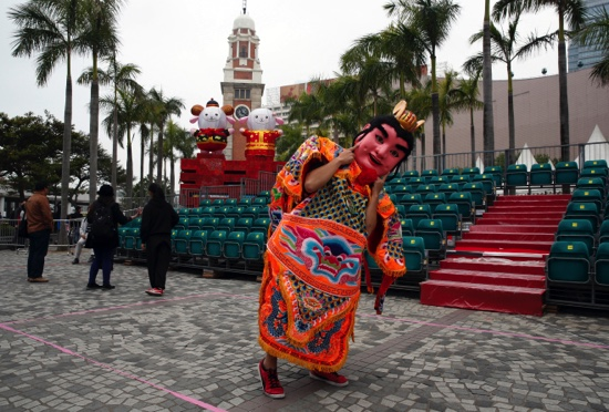 """A performer from Taiwan dressed as the """"Third Prince"""" poses for a photograph in front of the sheep decorations during the rehearsal for the International Chinese New Year Night Parade in Hong Kong"""