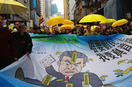 Pro-democracy activists carry a banner depicting Hong Kong Chief Executive Leung Chun-ying during a march to Central, demanding universal suffrage in Hong Kong Sunday, Feb. 1, 2015