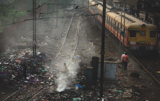 A train moves past burning garbage at a local train station in Mumbai, India