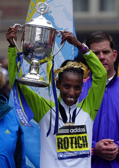 Caroline Rotich, of Kenya, lifts her trophy after winning the women's division of the Boston Marathon