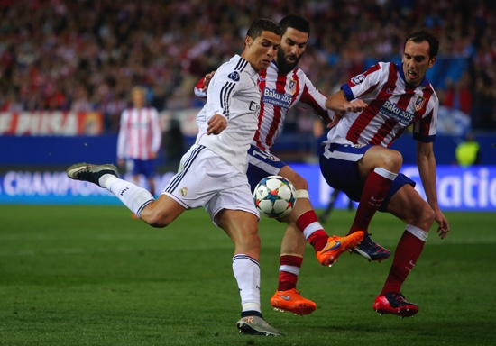 Real Madrid's Cristiano Ronaldo fights for the ball against Atletico's Diego Godin and Atletico's Arda Turan during the Champions League quarterfinal first leg soccer match between Atletico Madrid and Real Madrid at the Vicente Calderon stadium in Madrid, Spain