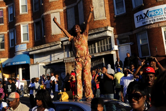 A woman stands on a car during a party in the street in Baltimore on Saturday