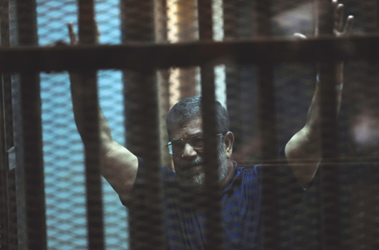 Ousted Egyptian President Mohammed Morsi raises his hands as he sits behind glass in a courtroom in an eastern Cairo suburb