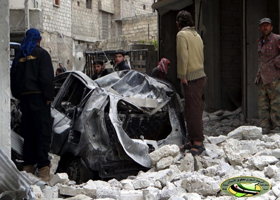 Syrians inspect a destroyed car after an airstrike, in Ansari neighborhood in Aleppo