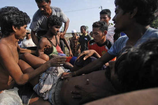 Migrants who were rescued by Acehnese fishermen are assisted by local residents to board a truck that is taking them to a hospital upon arrival in Simpang Tiga, Aceh province, Indonesia